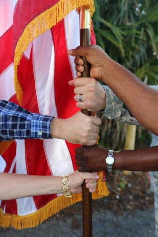 Five people with different ethnicities hold on the American flag.