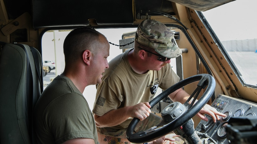 Army Specialist David Chaffin, instructor for the 133rd Battalion, shows Air Force Senior Airman Aiden Penrod, 380th Expeditionary Logistics Readiness Squadron ground transportation apprentice, the instrument panel of the M1075 Palletized Load System, July 22, 2020 at Al Dhafra Air Base, United Arab Emirates.