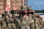Service members wearing face masks stand in a line with their right hands raised.