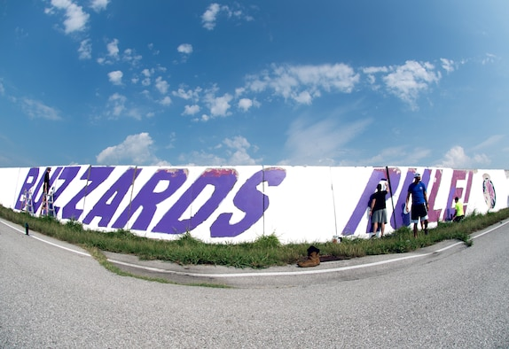 Airmen from the 510th Fighter Squadron and the 510th Aircraft Maintenance Unit paint a wall at Aviano Air Base, Italy, Aug. 13, 2020. Repainting the wall was part of the Buzzard Unity event which aimed to  boost morale and camaraderie.  (U.S. Air Force photo by Senior Airman Caleb House)