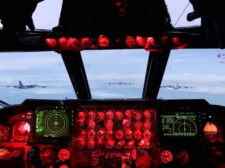 B-52s are seen flying in formation out of the window of a cockpit window