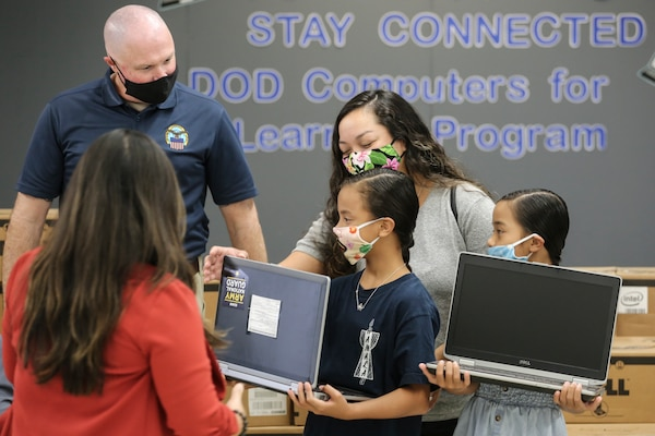 Students in Guam investigate new laptop computers.