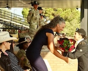 Woman receives flowers from Soldier