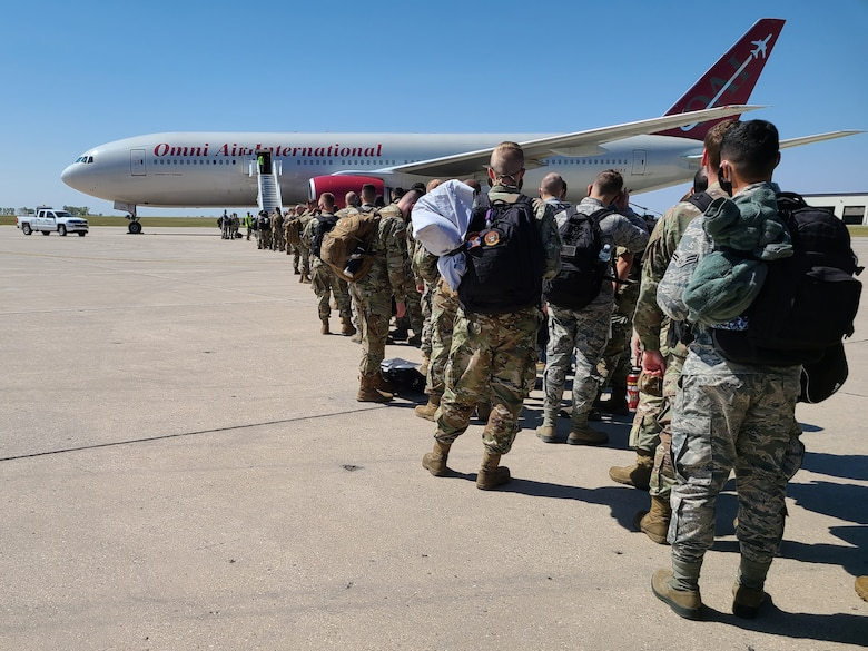 Airmen wait in line to board a jet for deployment