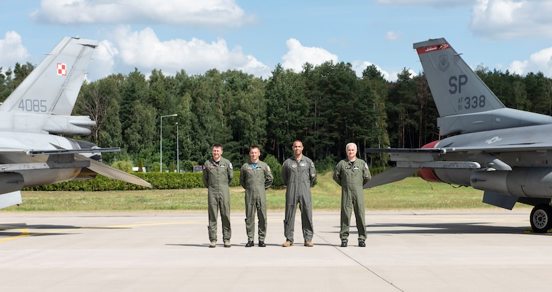 Starting far left, Polish air force Col. Tomasz Jatczak, 32nd Tactical Air Base commander, Brig. Gen. Iteneusz Nowak, 2nd Tactical Air Wing commander, U.S. Air Force Brig. Gen. Adrian Spain, United States Air Forces in Europe and Air Forces Africa director of plans, programs and analyses, and Polish air force Maj. Gen. Jacek Pszczoła, inspector of the Polish air force, pose in front of a static display, August 24, 2020, at Łask AB, Poland. The U.S. and Polish partnership is critical in light of growing security challenges, and opportunities to share perspectives and integrate help strengthen this relationship. (U.S. Air Force photo by Senior Airman Melody W. Howley)