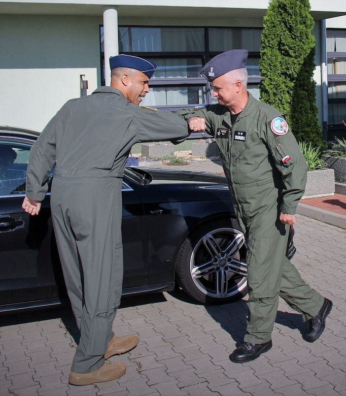 U.S. Air Force Brig. Gen. Adrian Spain, United States Air Forces in Europe and Air Forces Africa director of plans, programs and analyses, left, and  Polish air force Maj. Gen. Jacek Pszczoła, inspector of the Polish air force, bump elbows in place of handshakes during a tour of the 32nd Tactical Air Base, August 24, 2020, at Łask AB, Poland. The U.S. values the bilateral relationship with Poland and continues to share perspectives, train on missions and learn from each other. (Photo courtesy of the 32nd Tactical Air Base)