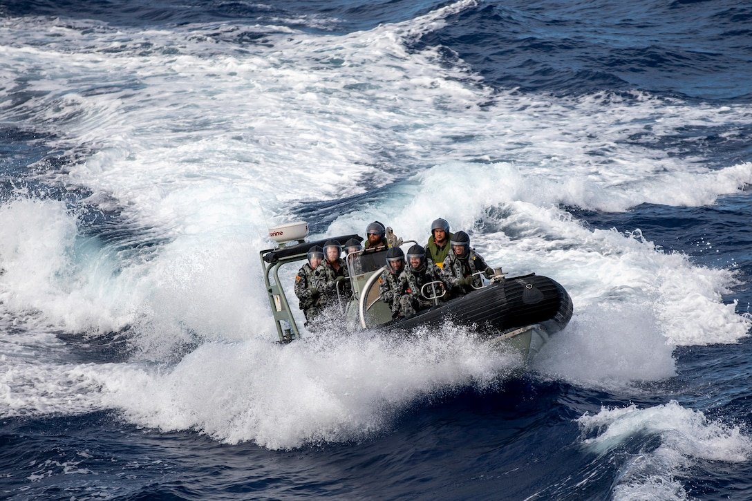 Sailors in small boat crest through the waves.