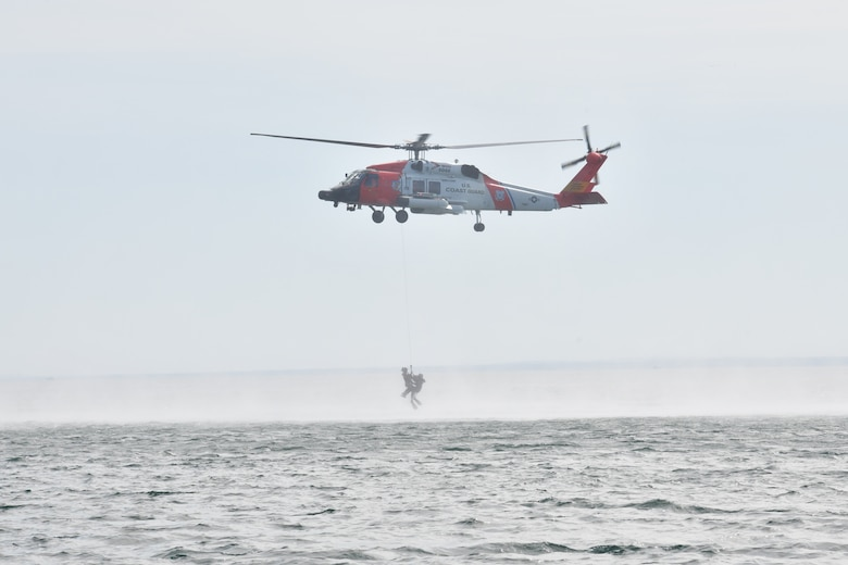 A U.S. Coast Guard MH-60 Jayhawk from Air Station Traverse City, Michigan hoists an F-16 pilot from the 148th Fighter Wing, Minnesota Air National Guard from Lake Superior, near Duluth, Minnesota during a water survival and rescue training mission.
