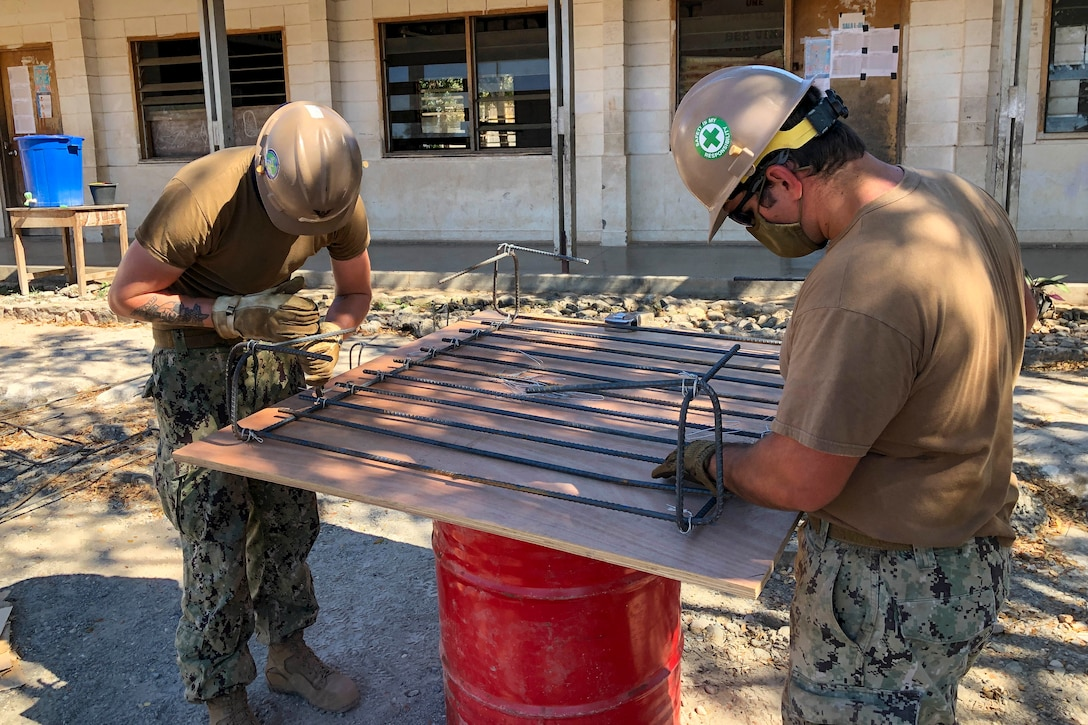Two sailors tie rebar during a construction project.