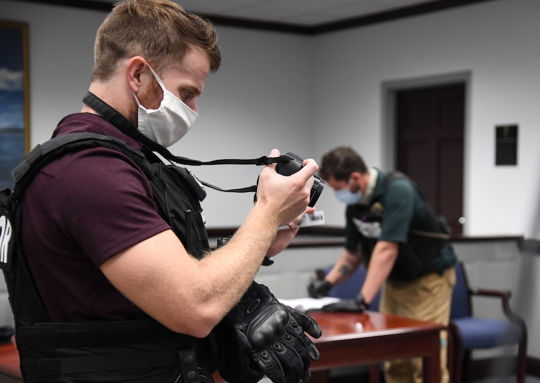U.S. Air Force Staff Sgt. Ryan Ingrassia, 81st Security Forces Squadron investigator, and Chris Soukup, 81st SFS detective, document the crime scene for evidence inside the Sablich Center during an active shooter exercise at Keesler Air Force Base, Mississippi, Aug. 20, 2020. The scenario included two active duty Air Force members who simulated opening fire inside the Sablich Center in order to test the base's ability to respond to and recover from a mass casualty event. (U.S. Air Force photo by Kemberly Groue)