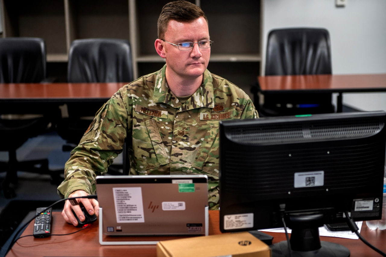 An airman works on a computer.