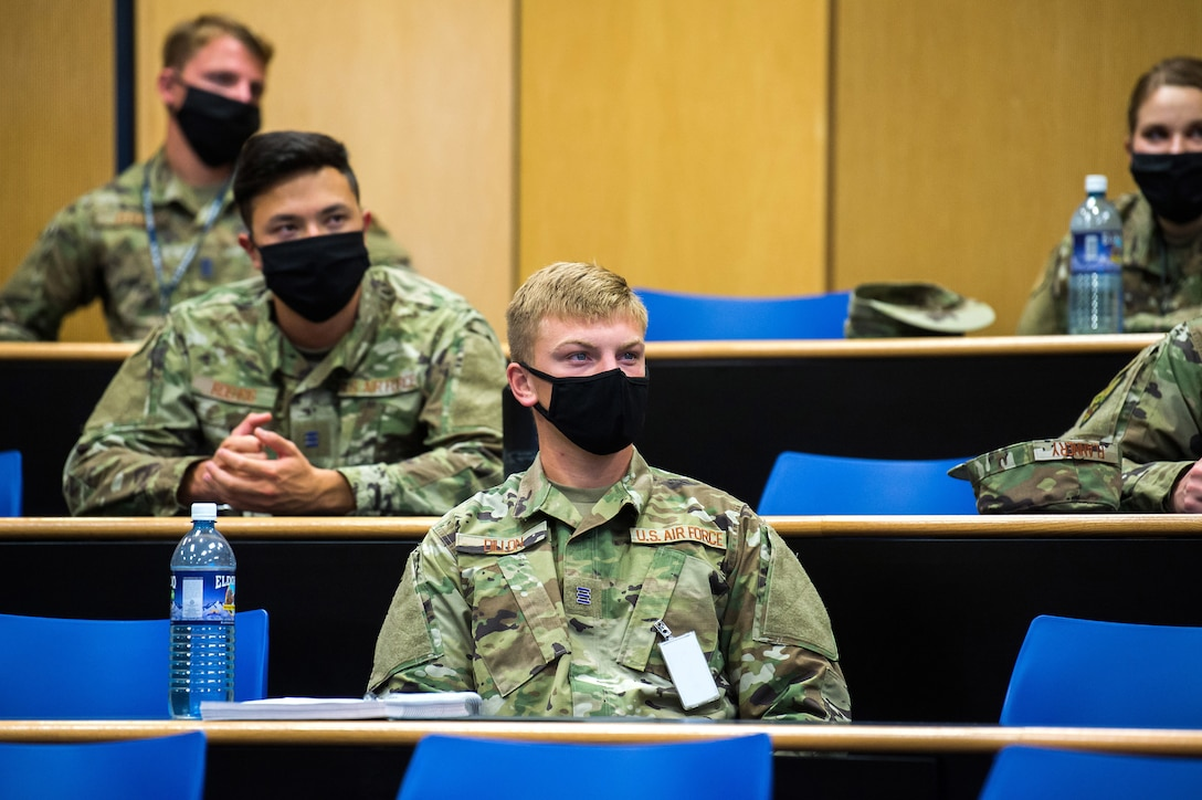 Masked students sit in a classroom.