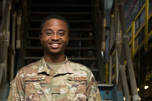 An Airman standing in front of a staircase smiles at the camera