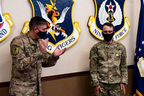 Photo of Airman getting congratulated by commander.
