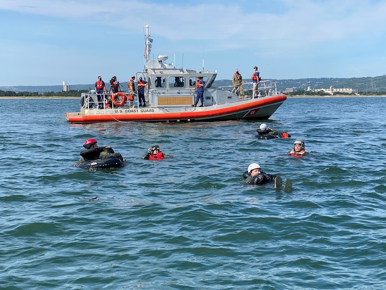 Pilots and aircrew flight equipment specialists with the 148th Fighter Wing, Minnesota Air National Guard, practice water survival techniques near a U.S. Coast Guard RBM-45628 from Coast Guard Station Duluth, while conducting a water survival and rescue training mission.