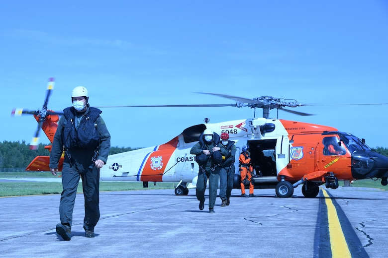 Pilots and aircrew flight equipment personnel from the 148th Fighter Wing, Minnesota Air National Guard exit a U.S. Coast Guard MH-60 Jayhawk from Air Station Traverse City, Michigan after being hoisted from Lake Superior during a joint water survival and rescue training mission near Duluth, Minnesota on August 25, 2020.