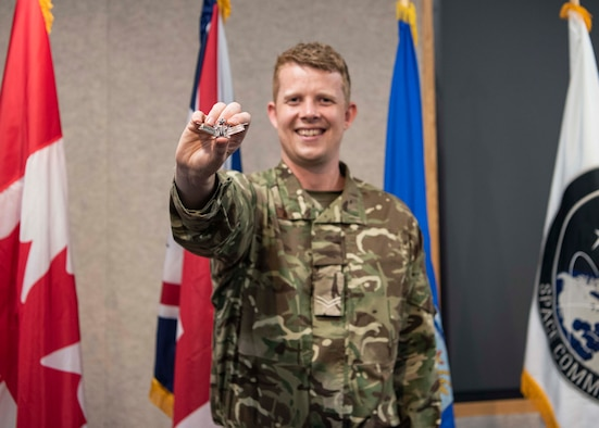 Photo of Cpl Mitchell Astbury holding up the Space Operations Badge he earned