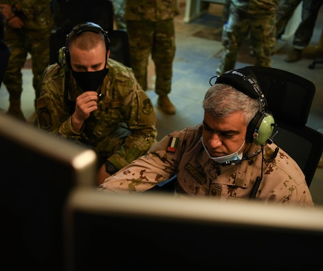 Airman 1st Class Derek Hilton (left), 727th Expeditionary Air Control Squadron weapons director, watches Col. Abdallah Ali Mohamed Al-Bloushi, United Arab Emirates Air Operations Center deputy commander, set up controls during a visit to the 727 EACS headquarters (Kingpin), August 24, 2020, in Al Dhafra Air Base, United Arab Emirates.