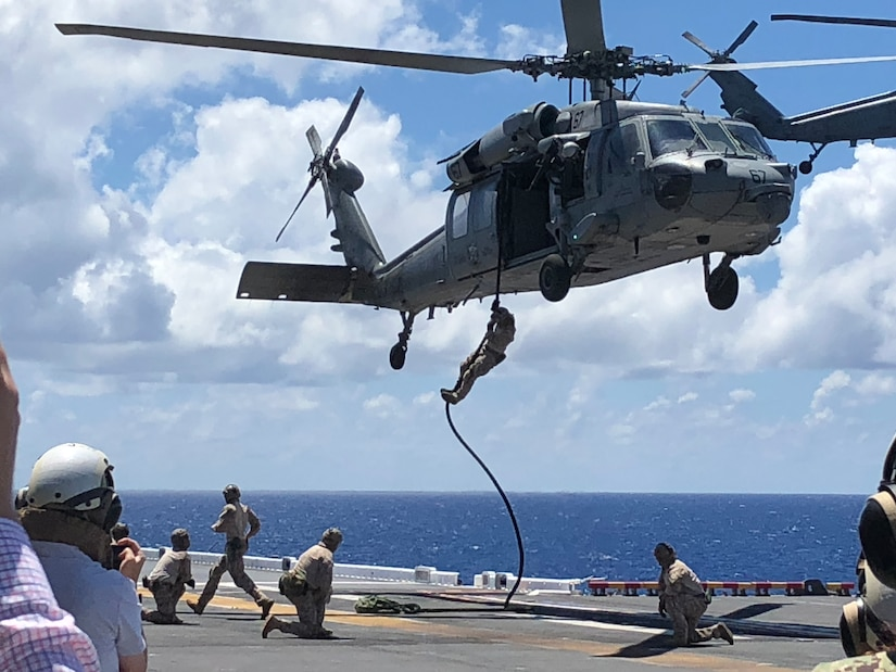 Sailors slide down a rope from a helicopter onto the flight deck of a ship.