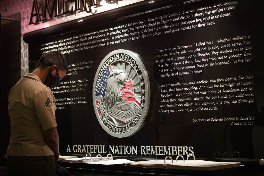 A U.S. Marine looks through a book of photography at America's Heroes Memorial during a professional development event in the Pentagon at Washington, D.C. on Aug. 13.