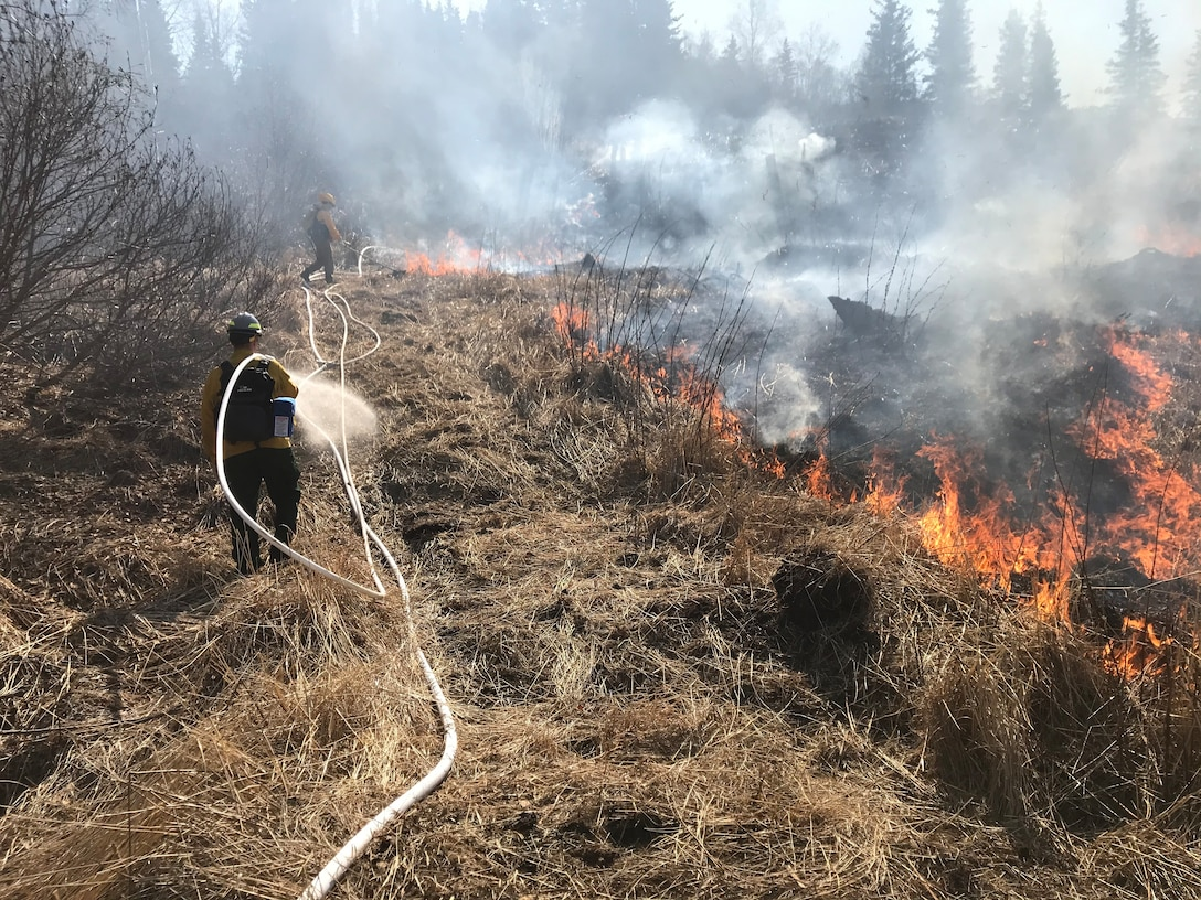 Two people lay hoses across dry landscape with fires and smoke in the distance.
