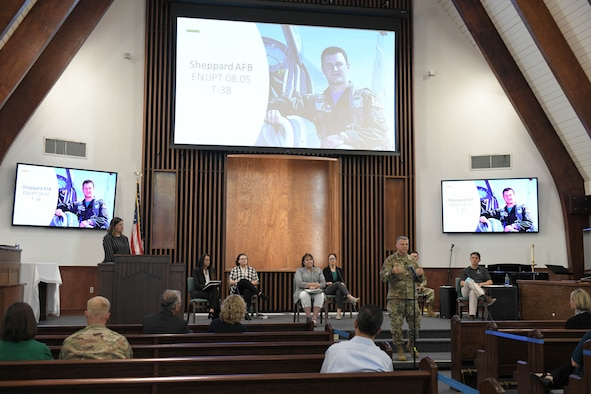 Photo shows Col. Moore standing at mic stand addressing audience with large screens behind him showing Capt. Nicholas Whitlock.