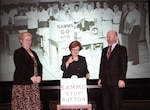 "Two women and a man stand in front of a sign that says ""SAMMS STOP BUTTON"" in front of a historical photo of a group of employees about to hit the ""SAMMS GO BUTTON."""
