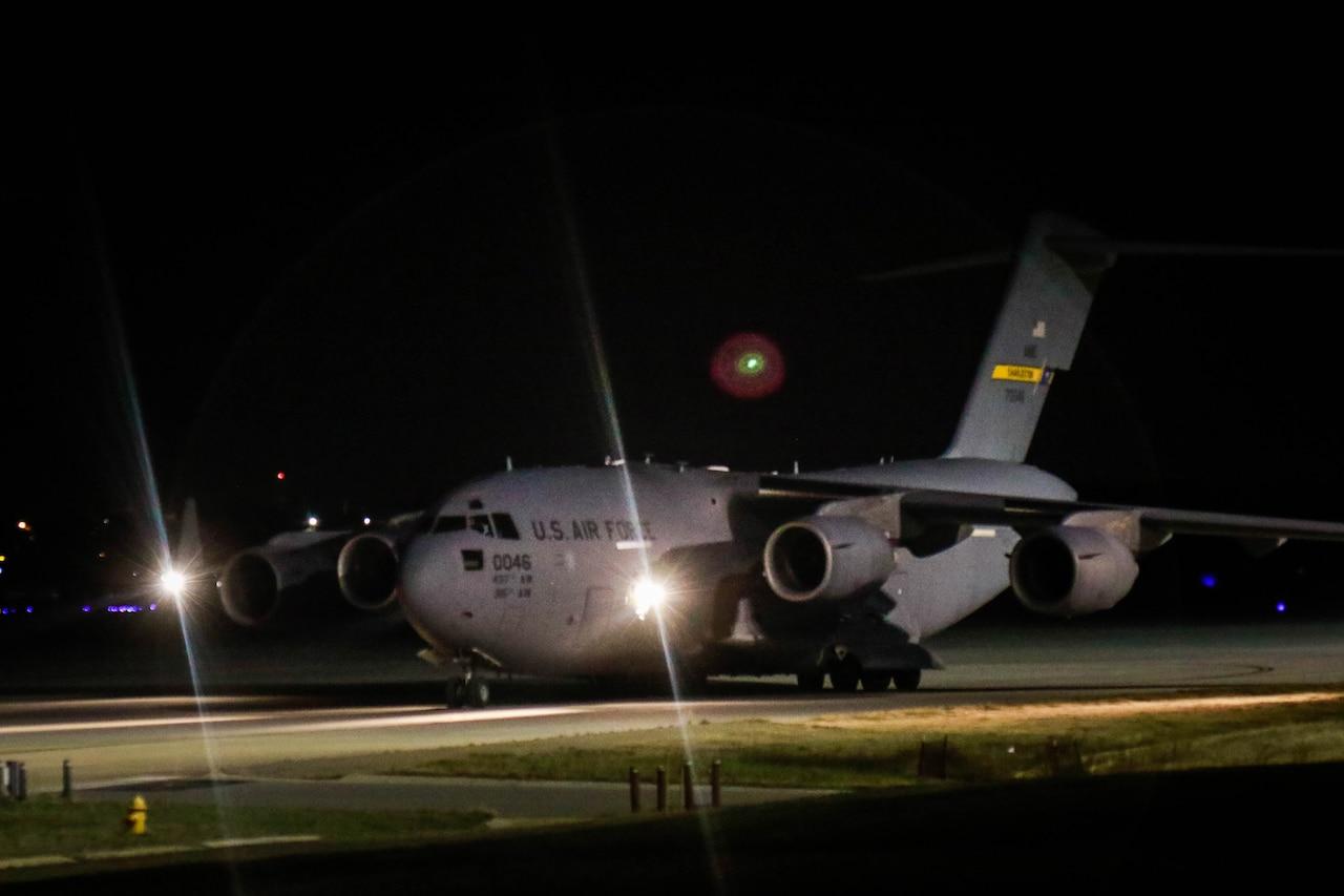 A large aircraft rolls across a runway.