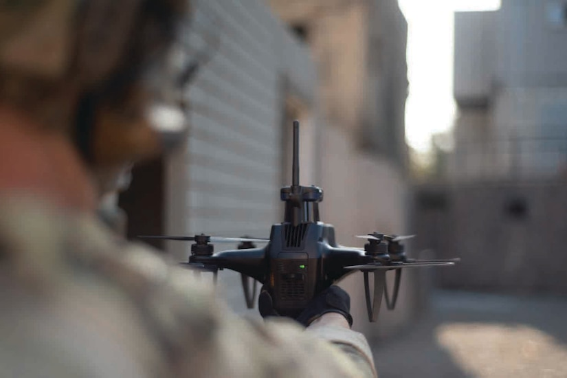 A hand holds a quadcopter drone.