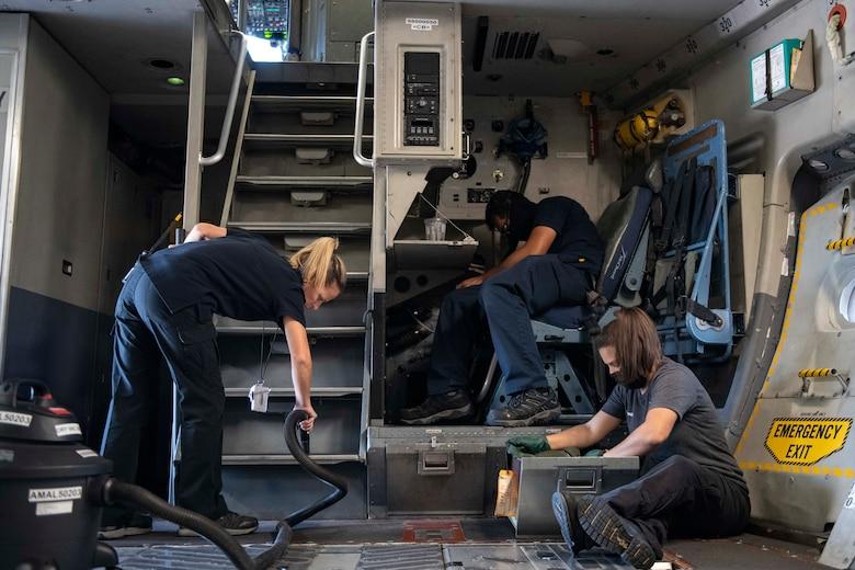 Aircraft attendants clean the inside of a C-17 Globemaster III.