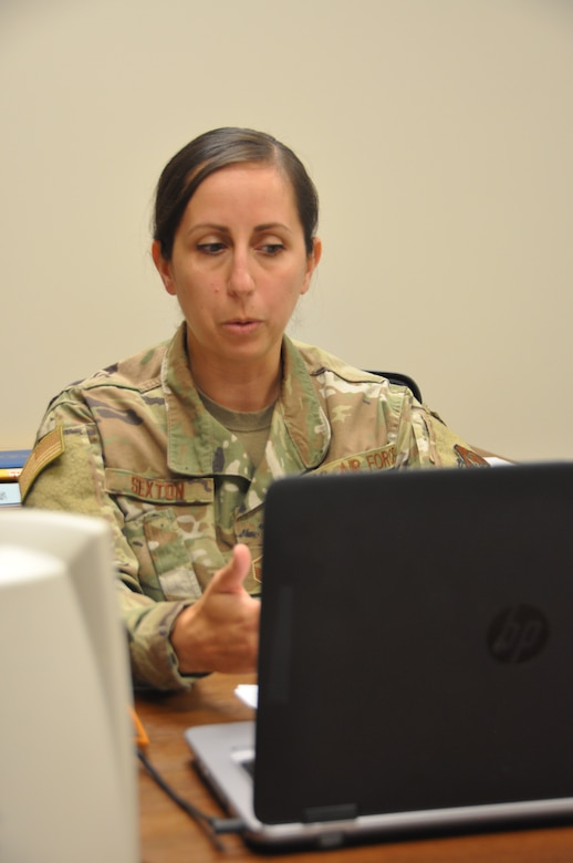 a person conducts a virtual class looking at a computer