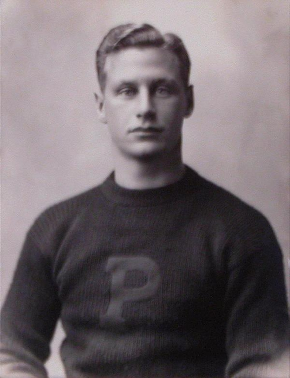 A man in a Princeton letter sweater poses for a photo.