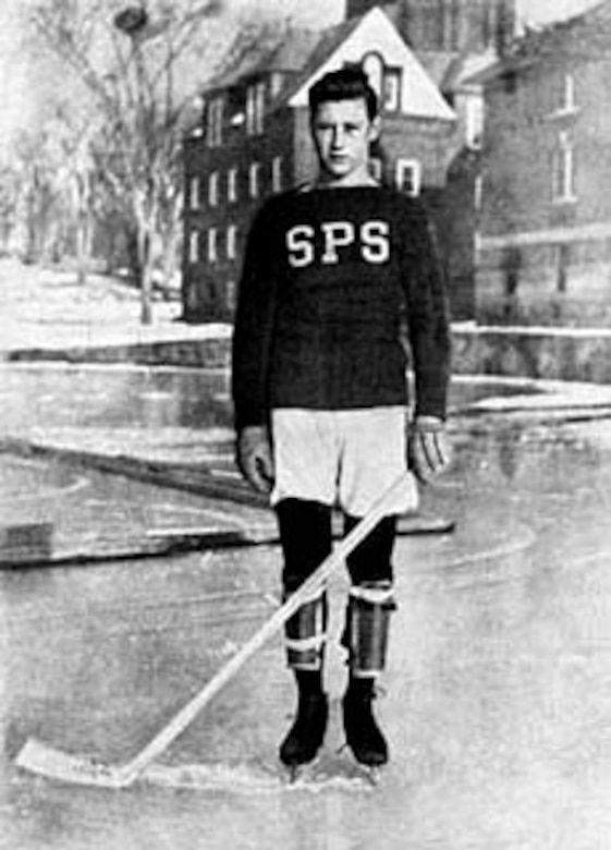 A young man in school hockey gear poses for a photo.