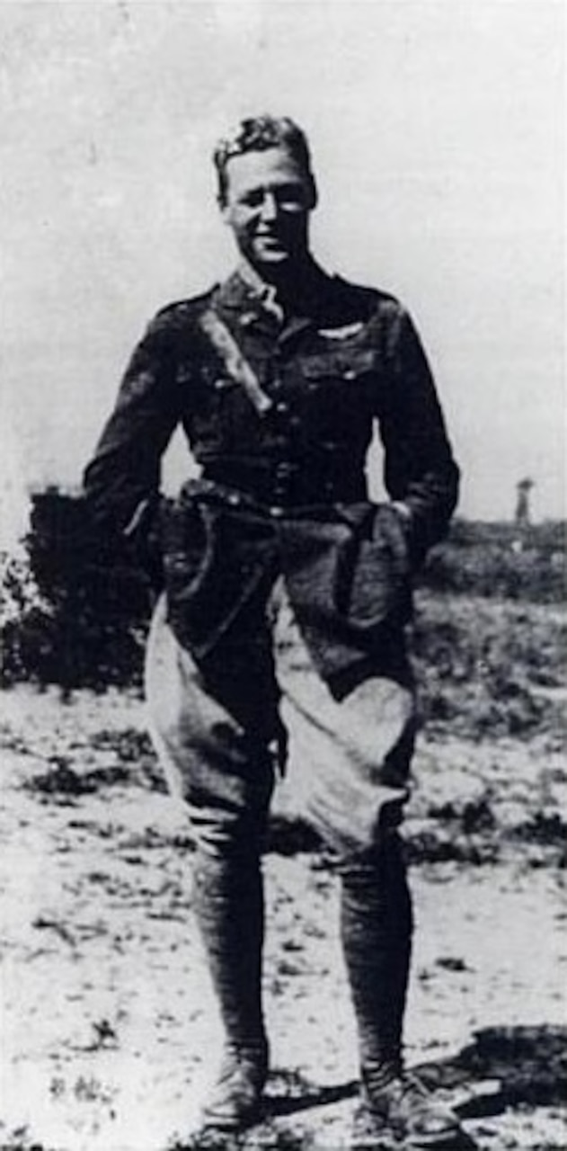 A man in an aviator uniform poses for a photo.