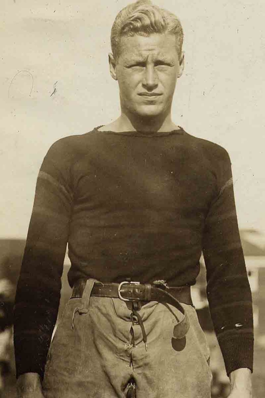 A man in a football uniform poses for a photo.