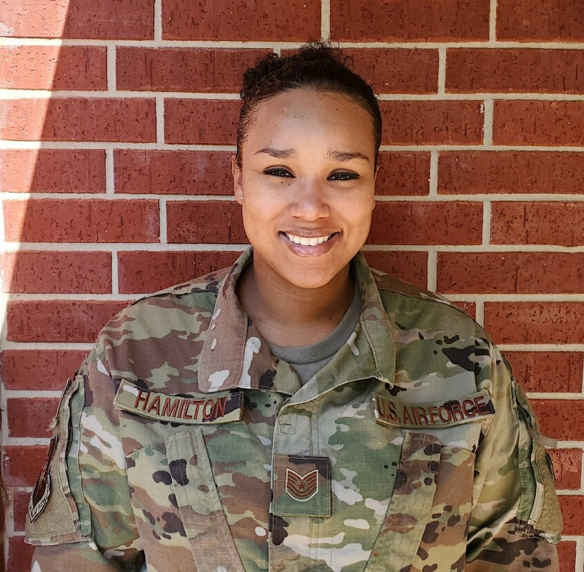Female airman in uniform, standing in front of brick wall