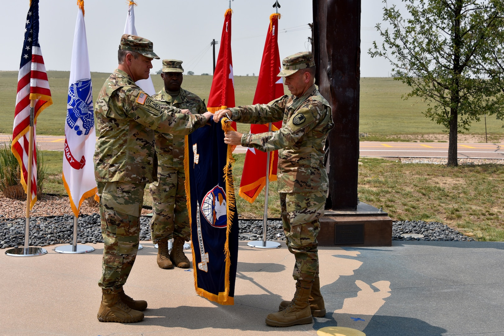 Gen. James H. Dickinson, U.S. Space Command commander, left, and Lt. Gen. Daniel L. Karbler, U.S. Army Space and Missile Defense Command commanding general, unfurl SMDC's colors to officially recognize the command as the Army Service Component Command to USSPACECOM during an. Aug. 21 ceremony at Schriever Air Force Base, Colorado.