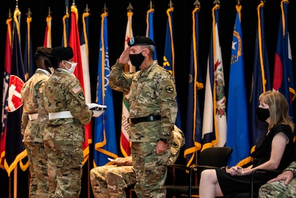 Maj. Gen. Steven W. Ainsworth, the outgoing commander of the 84th Training Command, receives the U.S. flag as his wife, Susanne, looks on during his relinquishment-of-command and retirement ceremonies, Aug. 22, 2020, at Fort Knox, Ky.
