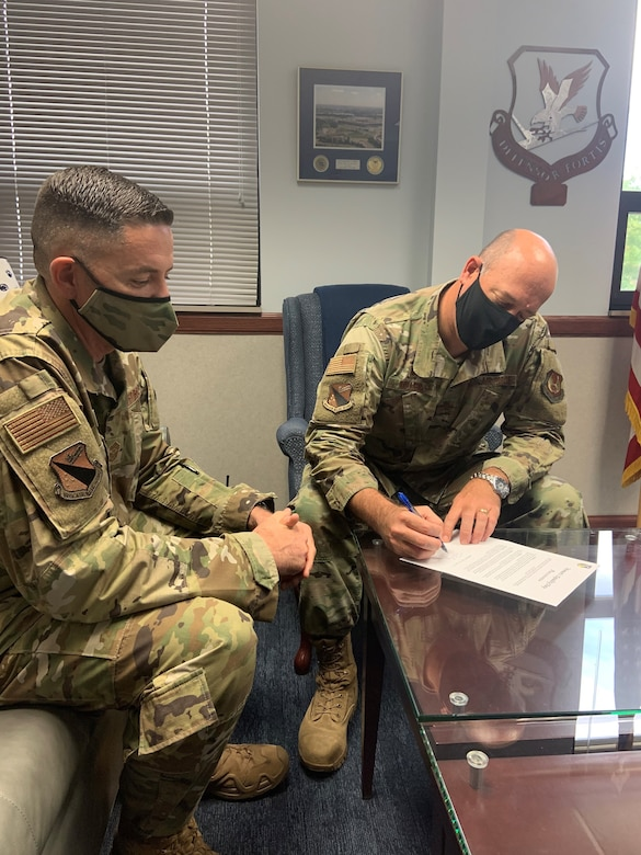 Chief Master Sgt. Jason Shaffer (left), 88th Air Base Wing command chief, looks on while Col. Patrick Miller, 88th Air Base Wing and installation commander, signs a proclamation for Women's Equality Day on Aug. 26. This year's theme for Women's Equality Day is 'Beyond the Scope of Women's Suffrage: 100 Years of Progress,' marking the 100th anniversary of the signing of the 19th Amendment affording women the right to vote. (U.S. Air Force photo/Stacey Geiger)