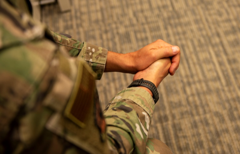 Over-the-shoulder view of an Airman with their hands together.
