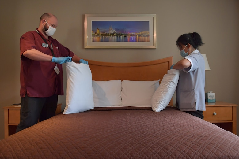Two people changing pillow cases.