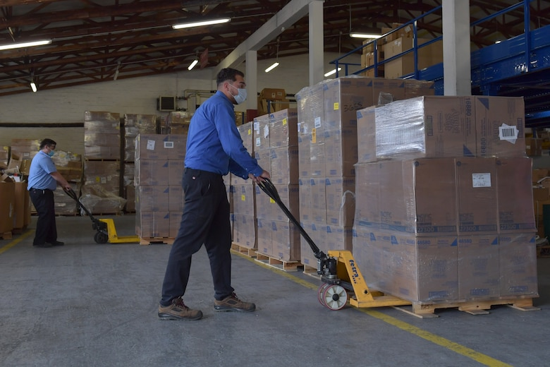 Two people moving pallets of boxes in a warehouse.