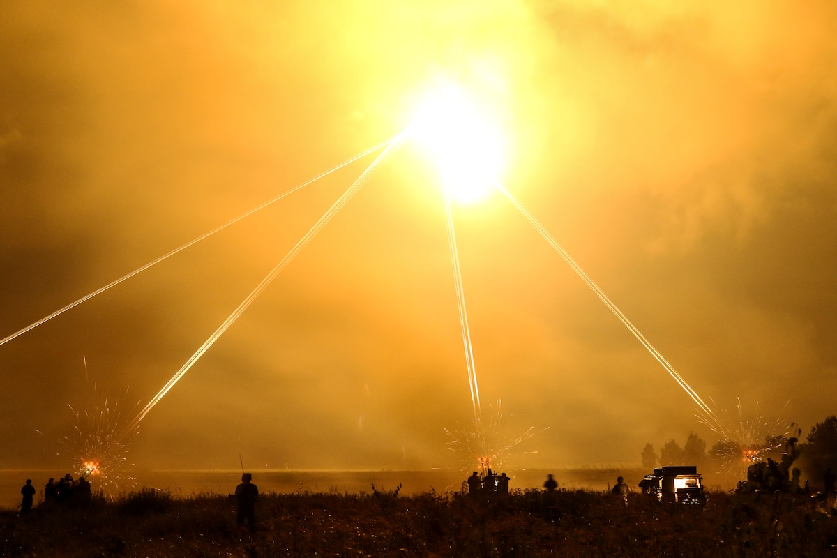Service members in silhouette on the ground fire weapons that light up a yellowish sky.