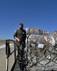 Senior Master Sgt. Bryan Fehrenbach (left) and Senior Airman Madison Doherty (right), 924th Air Refueling Squadron boom operators and load masters, haul a cargo pallet onto a KC-46A Pegasus assigned to McConnell Air Force Base, Kansas, Aug. 15, 2020, at Travis Air Force Base, California. This was the first Reserve-lead cargo load utilizing the KC-46.