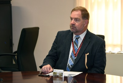 DLA Disposition Services Director Mike Cannon sits at a  conference table.