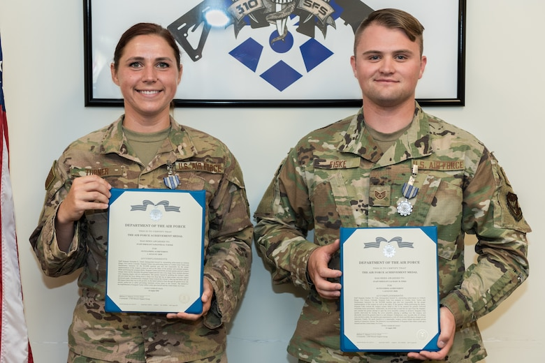 A man and a woman standing next to each other holding award citations.