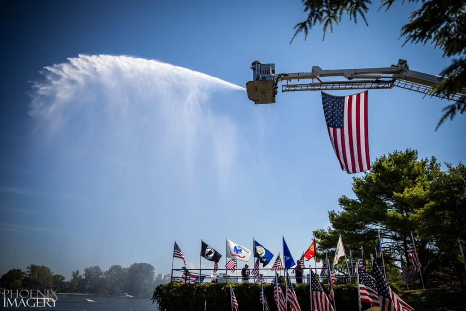 Firetruck spraying water over a lake with flags displayed on an overlook.