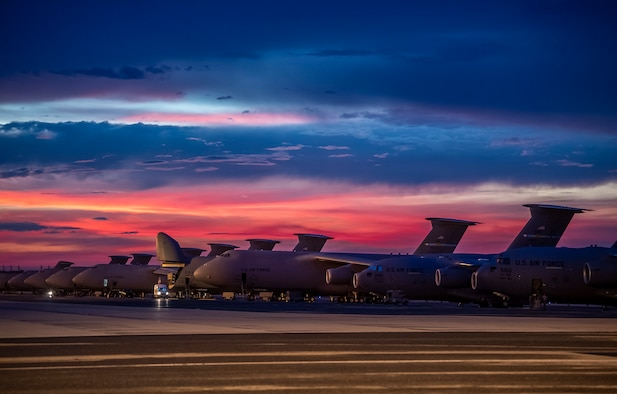 The sun sets over Dover Air Force Base, Delaware, as Airmen work on the flight line Aug. 12, 2020.  The 436th Airlift Wing generates global strategic airlift with both C-5M Super Galaxy and C-17A Globemaster III.  (U.S. Air Force photo by Senior Airman Christopher Quail)