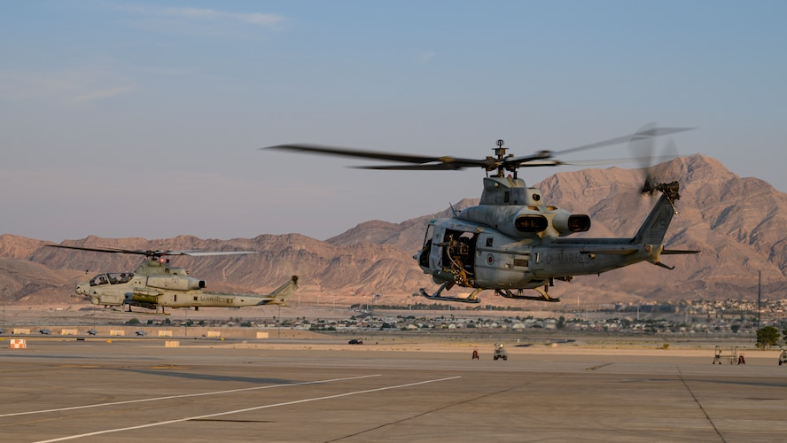 Helicopters take off from the flight line.
