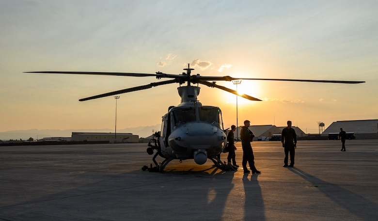 Marines stand next to helicopter on flight line.